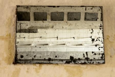 terezin: Terezin, Repubblica Ceca - 8 ottobre 2010: Una vista di una fila di lavandini in bagno modello al campo di concentramento di Terezin nella Repubblica ceca. La vista si riflette attraverso uno specchio antico che sta perdendo il suo rivestimento riflettente argento.