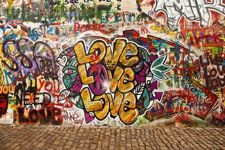 grafitis: Praga, República Checa - 7 de octubre de 2010: Una sección del muro de Lennon en el área pequeña ciudad de Praga, cerca del Puente de Carlos. Este muro histórico está abierto a la pintada pública en memoria de John Lennon.