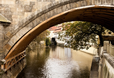 exist: Underneath the landmark Charles Bridge in Prague, a number of small canals exist to serve some of the old mills such as the one powered by the water wheel at the end of the canal