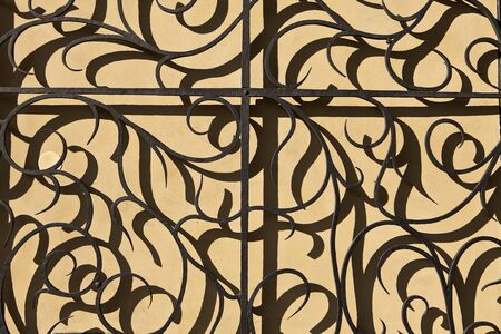 A detail view of a portion of a wrought iron gate on the grounds of Prague Castle  The repetitive nature of the shadows against a painted wall make this a nice background  photo