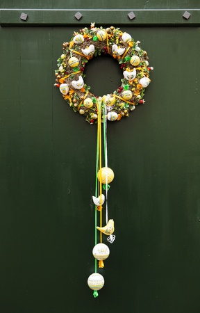A traditional Czech wreath hanging on a green door  It is made with tree branches and filled with ornamental decorations such as birds, balls, ribbons, and more  Imagens