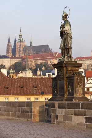 tripartite: The statue of Saint John of Nepomuk on the Charles Bridge in Prague with the castle and St. Vitus Cathedral in the background. The saint is presented in a traditional way, as a bearded capitulary with a five-star glory, standing on a tripartite base.