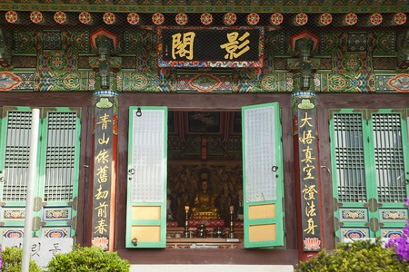 bongeunsa: Seoul, Korea - April 26, 2012:  One of the smaller buildings at the Bongeunsa Buddhist temple in Seoul, South Korea. The figure of the Buddha is visible in all his splendor through the entrance door