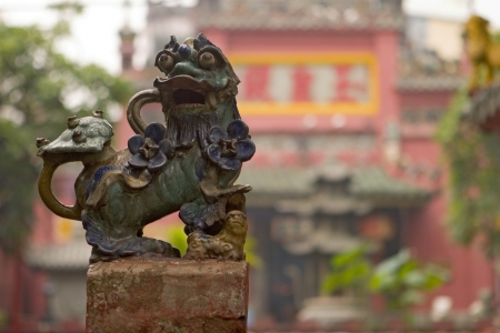 A Chinese lion guarding the front gate of a Buddhist temple in Ho Chi Minh City (Saigon) in Vietnam. Stock Photo