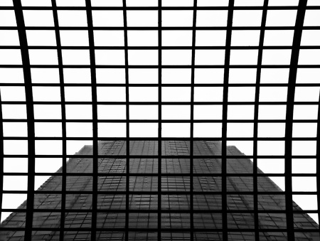A symmetrical abstract view of the sky and a skyscraper through a glass roof at a shopping center in Tokyo. In pure black and white. photo