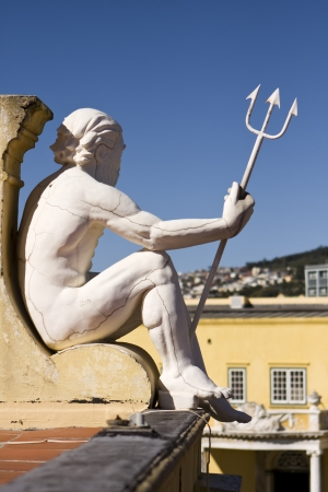 A statue of Neptune holding a trident that is looking over a courtyard on the roof of the Castle of Good Hope in Cape Town, South Africa  Looking closely, a series of cracks are visible throughout sculpture