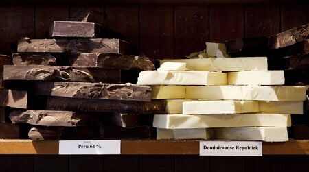 Chunks of white and dark chocolate from different points of origin are for sale in a candy store  photo