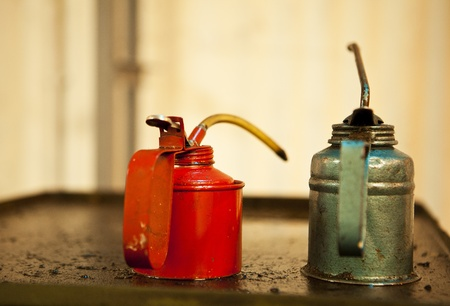 Two cans of machine oil, one red and one green, rest on top of an old piece of greasy machinery that was used to make ammunition at the Ayalon Institute in Israel. Banco de Imagens