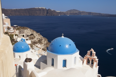thera: Classic view of blue-painted domes on Orthodox Greek churches in the town of Oia on the island of Santorini in the Greek Islands  The town of Thera is in along the island rim in the background