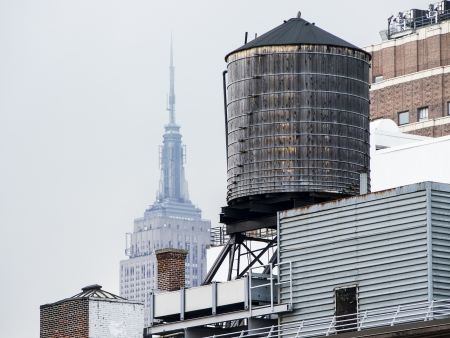 distant: On a hazy day in New York, The Empire State Building rises in over a classic wooden water tower on the roof of a building  Editorial