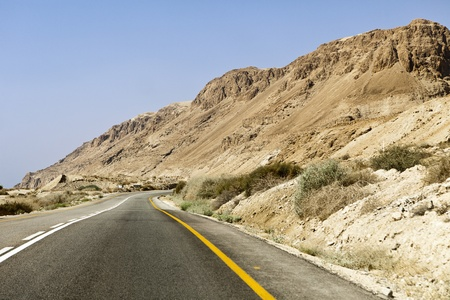 With the Dead Sea Mountains on the right, a two-lane highway twists through the desert  photo