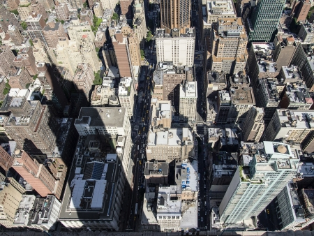 extends: On a sunny day, the shadow of the Empire State building extends over blocks of buildings throughout midtown Manhattan in New York City