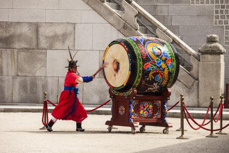 SEOUL, KOREA - APRIL 27, 2012: A guard is strking a giant ceremonial drum during the changing of the guard ceremony at the Gyeongbokgung Palace complex in Seoul, Korea on April 27, 2012. Editorial