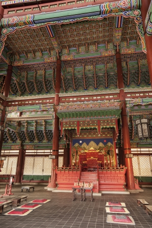 SEOUL, KOREA - April 27, 2012: Geunjeongjeon Hall holds the royal throne room of the Gyeongbokgung Palace complexin Seoul Korea. The ornate decorations of the hall are painted in bright red and green colors.