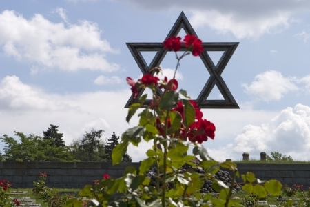 Terezin, Czech Republic - July 3, 2007: The Star of David rises over the cemetery in front of the walls of the Terezin (or Theresienstadt) prison. The flowers are planted at every grave marker.