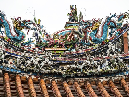 buddhist temple roof: The roof of the entrance pagoda to the Mengjia Longshan Temple in Taipei is covered with brightly colored and complex traditional ornamental figures of dragons and other creatures.