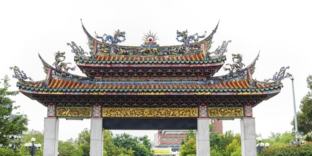 gatehouse: Taipei, Taiwan - November 10, 2012: The traditional, heavily decorated gate for the entrance to the Mengjia Longshan Temple in central Taipei on Taiwan. The temple combines several religions including Buddhism, Taoism, and Matsu.