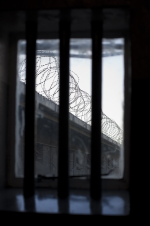 dismal: A bleak and dismal view through a prison window. The bars over the window with the only view of coils of barbed wire on a wall is symbolic of the lack of freedom for prisoners. Stock Photo