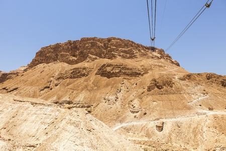 The historic landmark of the Masada plateau is eaily reached by a gondola using overhead cables that stretch from the base to the top. The alternative hiking trail winds up the mountain at the right. photo