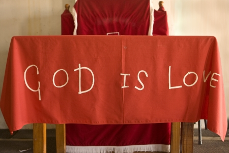 township: A handmade cloth saying God Is Love  This covers the altar of a make-shift church in the township of Kayamandi, South Africa