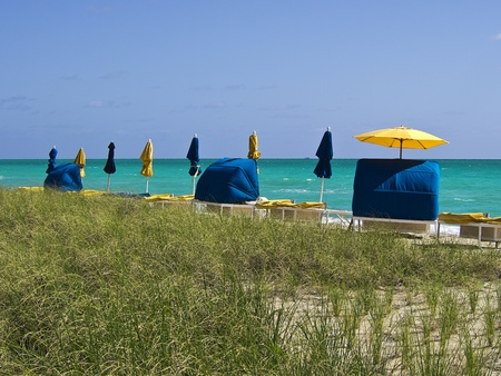 A row of beach cabanas with yellow and blue sun umbrellas line a beach in southern Florida on a sunny day. photo