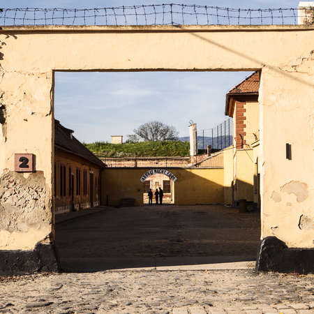 Terezin, Czech Republic - October 8, 2010: The entrance to the administrative area of the Little Fortress at the Theresienstadt concentration camp. At the end, the sign of Arbect Macht Frei (Labour Makes You Free) is visible over shadows of people. Stock Photo - 19994567