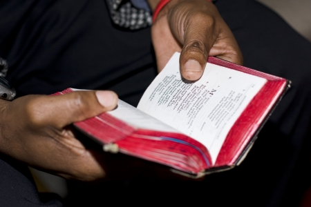 Wallacedene, South Africa - August 13, 2009  Two hands holding a well-used prayer book at a Methodist church service on Sunday are symbolic of faith of South African people  Note  shallow depth of field is focused on just the thumb and the nearby text