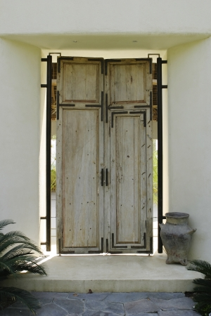 mezuzah: An antique wood front door for a Mexican house  The light from the open-air courtard behind is splashing around the edges of the door