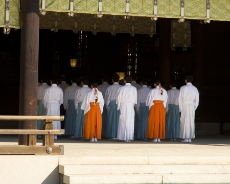 priest's ritual robes: A group of priests are lined up into five rows of five people each, receding into the shadow of the inner sanctuary of the temple  This was viewed at a traditional Shinto temple in Japan