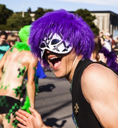 energetically: SEATTLE, WA - JUNE 22, 2013  A man with a mask and purple wig yells energetically while taking a break from pedaling the Tubaluba band float during the 2013 Annual Fremont Summer Solstice Parade in Seattle on June 22, 2013  The parade celebrates the start