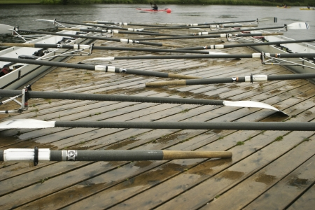 Two racing shells by the dock with oars at rest prior to a rainy practice  写真素材
