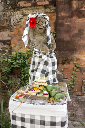 legian: A stone statue, dressed in a traditional checked cloth and a flower, has received a number of food offerings from worshippers