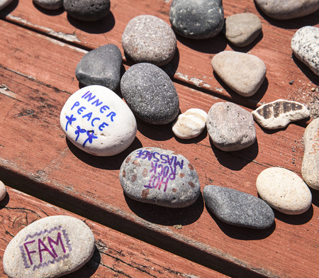 Rocks with writing and drawings are scattered across a red picnic table as they are being used in a family art project