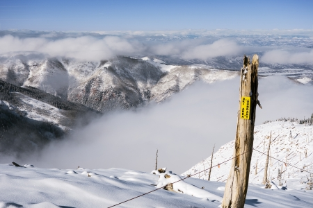 A warning sign marking the boundary between a ski area and a wid-open vista of Colorado mountains over cloads in winter  Stock Photo
