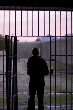 confine: Robben Island, South Africa - August 3, 2008  The outline of a man, at sunset, exiting through the iron bars into the prison yard of a jail in South Africa