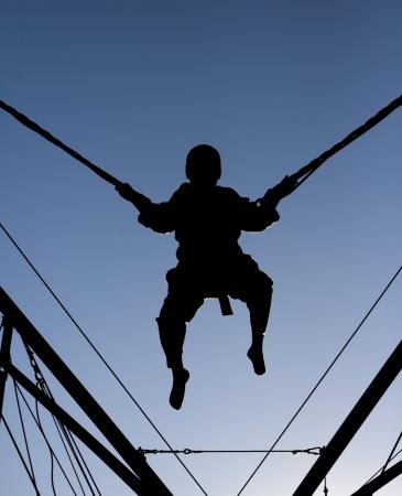 bungee jumping: Ciudad del Cabo, Sudáfrica - 17 de agosto 2008 Un negro silueta de un muchacho de salto y de ser suspendido en el aire por cuerdas elásticas