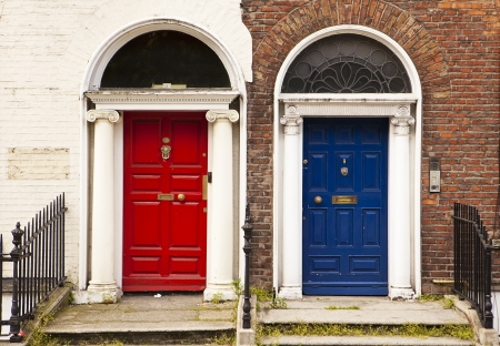 Two painted doors in Dublin stand side by side providing a colorful view  With a red and blue door complimented by traditional and whitewashed brick walls, the contrast is interesting  photo