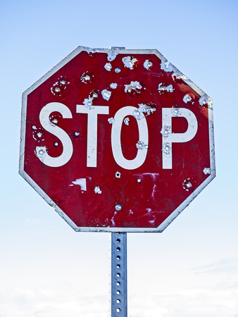 A red traffic stop sign riddled with bullet holes highlighted against a light blue sky