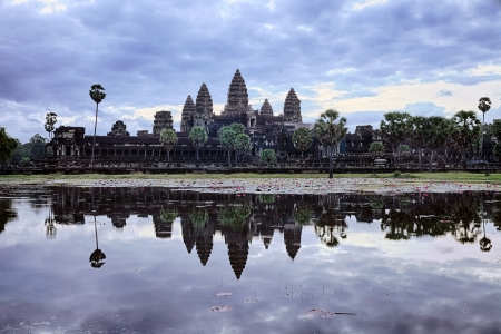 Sunrise over Angkor Wat  The towers of the ancient temple are reflected in the calm lake in front of the building