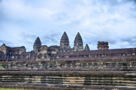 The first outside wall of Angkor Wat rises in front of the three tiered temple  The five towers of the quincunx are visible against a cloudy morning sky  photo