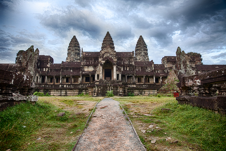 angkor wat: Dramatic cloudy skies show over Angkor Wat as seen from path at the rear entrance to the three-tiered pyramid temple  The five towers, or quincunx, of the historic site are visible  Stock Photo