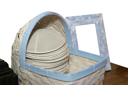 A woven basket filled with a stack of grey kippot  or yarmulkas  set aside for participants at a Jewish ceremony  In the background, an empty picture frame is waiting for the invitation or a picture  photo