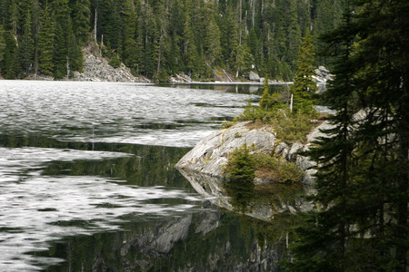 breaking up: In late spring, the surface of Lake Dorothy in the Washington Cascades is still barely covered with ice  The frozen surface of this alpine lake high in the mountains is just breaking up with the spring thaw for the summer