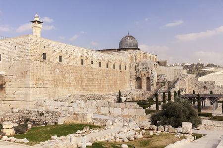 The walls of the Temple Mount in the Old City of Jerusalem in Isreal  Over the tall walls, the dome of the Al-Aqsa mosque and a minaret are visible