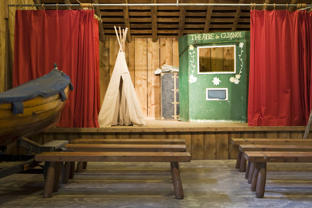 stage props: Canoe Island, United States - June 21, 2008  A theater at a summer camp that is used for occasional performances  The stage has a few props including a teepee, a booth, and a boat for use by the actors