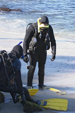 La Jolla, Kalifornien - 20. Oktober 2006 Zwei Taucher der Vorbereitung für einen Tauchgang an einem südlichen Strand von Kalifornien Die Taucher machen einen letzten Check auf ihre Ausrüstung, bevor sie ins Wasser