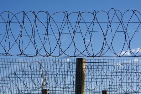 robben island: Coils of barbed wire on top of a fence provide security at a penitentiary in South Africa  The barb wire is symbolic of protection and security -- but also of the freedom that lies beyond the perimeter of the prison walls  Stock Photo