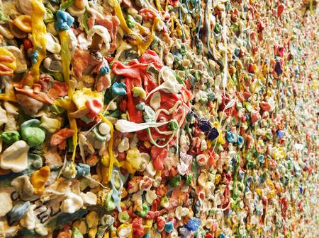 goma de mascar: Una vista de detalle de una parte de la famosa pared de chicle en Post Alley cerca el mercado Pike Place en Seattle Este hito se ha acumulado capas de goma de mascar en los últimos años en el modelo abstracto colorido Editorial