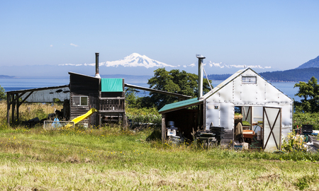 san juan: Two small outbuildings on a small organic farm on Waldron Island in Washington State  Mt  Baker is visible in the background