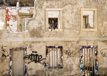 Lisbon, Portugal - October 10, 2011  Lisbon s run-down buildings are often covered in decorative graffiti including this semi-demolished structure with a replica of Dorothea Lange s Migrant Mother photograph seen through a window